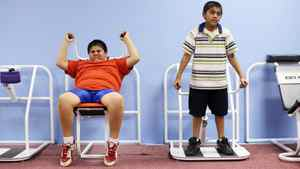 Weighing in at 68kg , Prashant Kumar, left, age 8, works on an exercise machine on Nov. 29, 2006 with his brother Prakeet, who comes to the gym with Prashant for support, at the Youth Visions Fitness Center in Upper Marlboro, Maryland.