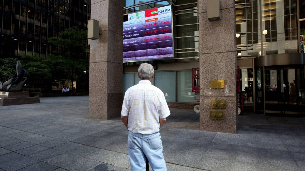 File photo of a man watching the Toronto stock market activity on a screen posted at 121 King Street in Toronto's financial district.