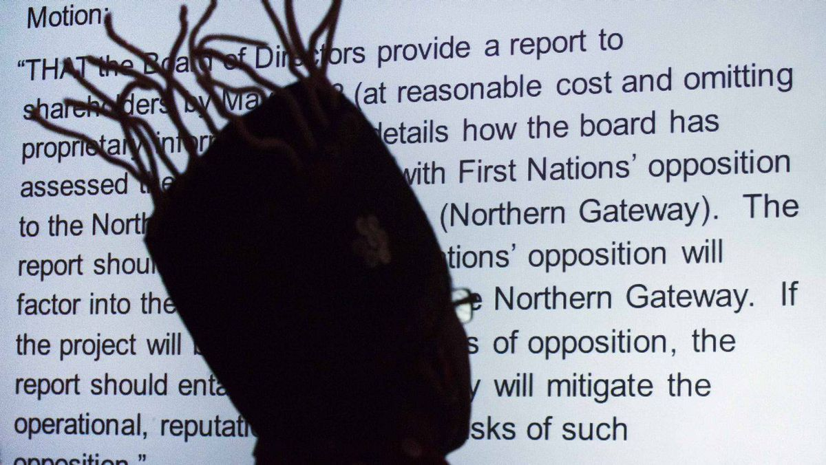 "During the meeting, Chief Na'Moks is silhouetted against a shareholders' proposal, displayed on a video screen, about the investment risks ""associated with First Nations' opposition to the Enbridge Northern Gateway pipeline."""