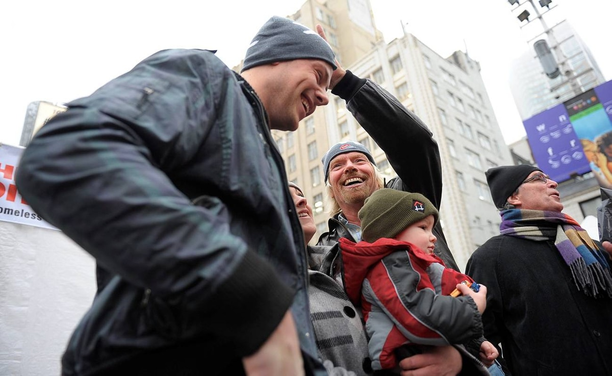 Sir Richard Branson grabs Cory Monteith's toque during a charity event for homeless youth at Yonge and Dundas Square in downtown Toronto.