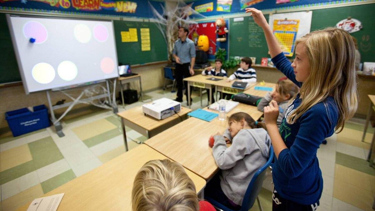 Abbie Chandler throws a ball at a smart board during a math lesson.