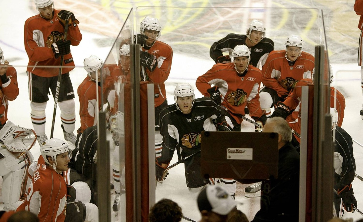 Chicago Blackhawks watch head coach Joel Quenneville diagram a practice drill during the first practice and scrimmage of the year at the United Center on Saturday Sept. 18, 2010 in Chicago. (AP Photo/Charles Cherney)