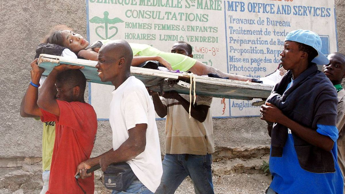 Haitians carry an injured person on Jan. 13, 2010 in Port-au-Prince.