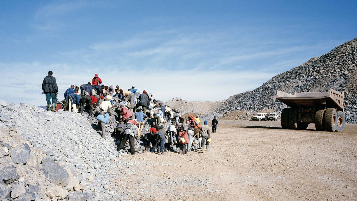 Intruders fall upon rocks left by a mine truck searching for gold. (North Mara Mine, Tanzania)