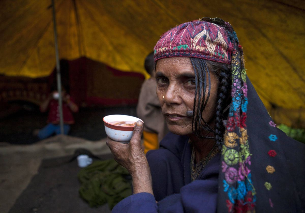 Zeba, a Kashmiri Bakarwal nomad, drinks tea inside her tent on the outskirts of Srinagar, India. Bakarwals are nomadic shepherds of the Jammu Kashmir state who wander in search of good pastures for their cattle.