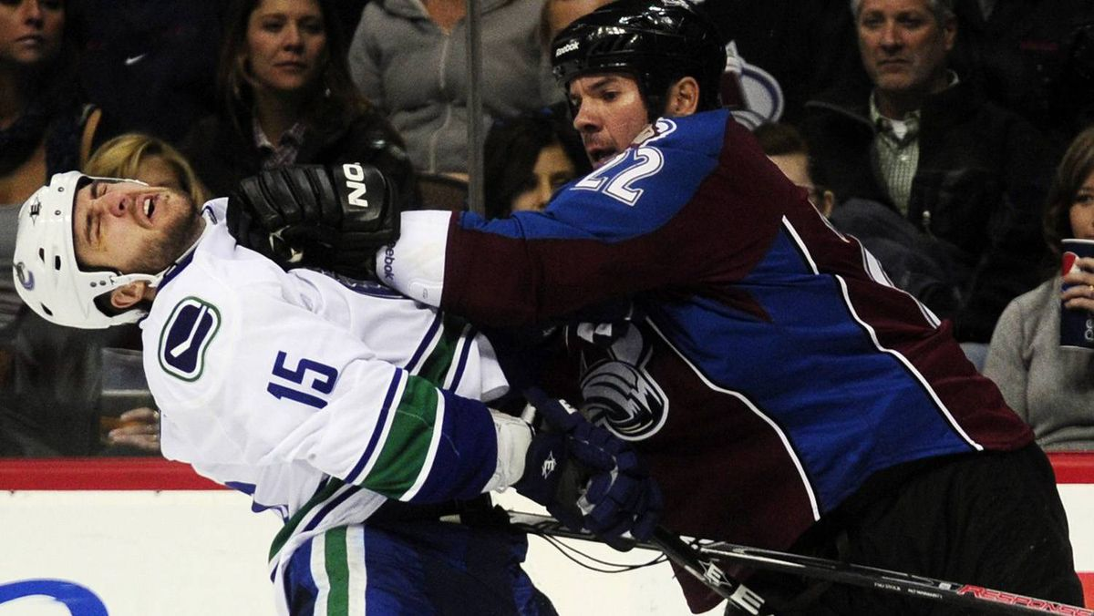 Colorado Avalanche defenceman Scott Hannan, right, pushes Vancouver Canucks centre Tanner Glass during the second period of an NHL hockey game in Denver on Thursday.