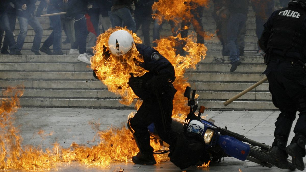 A policeman is seen in flames as he tries to escape after a petrol bomb was thrown at him during riots in front of the parliament in Athens on Feb. 23, 2011.