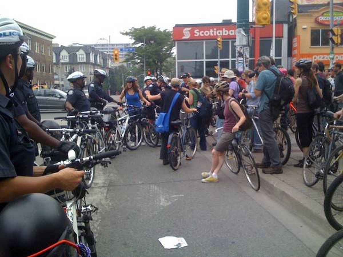 Photo of protesters aboard bikes chanting 'let us ride!' as they try to break through police barricade at Bloor and Spadina in Toronto, Sunday June 27.