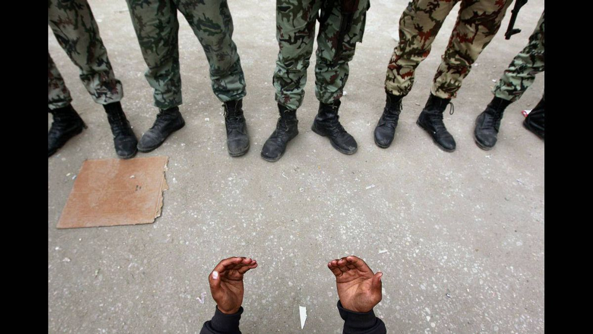 An opposition demonstrator prays in front of army soldiers near Tahrir Square in Cairo February 5, 2011.