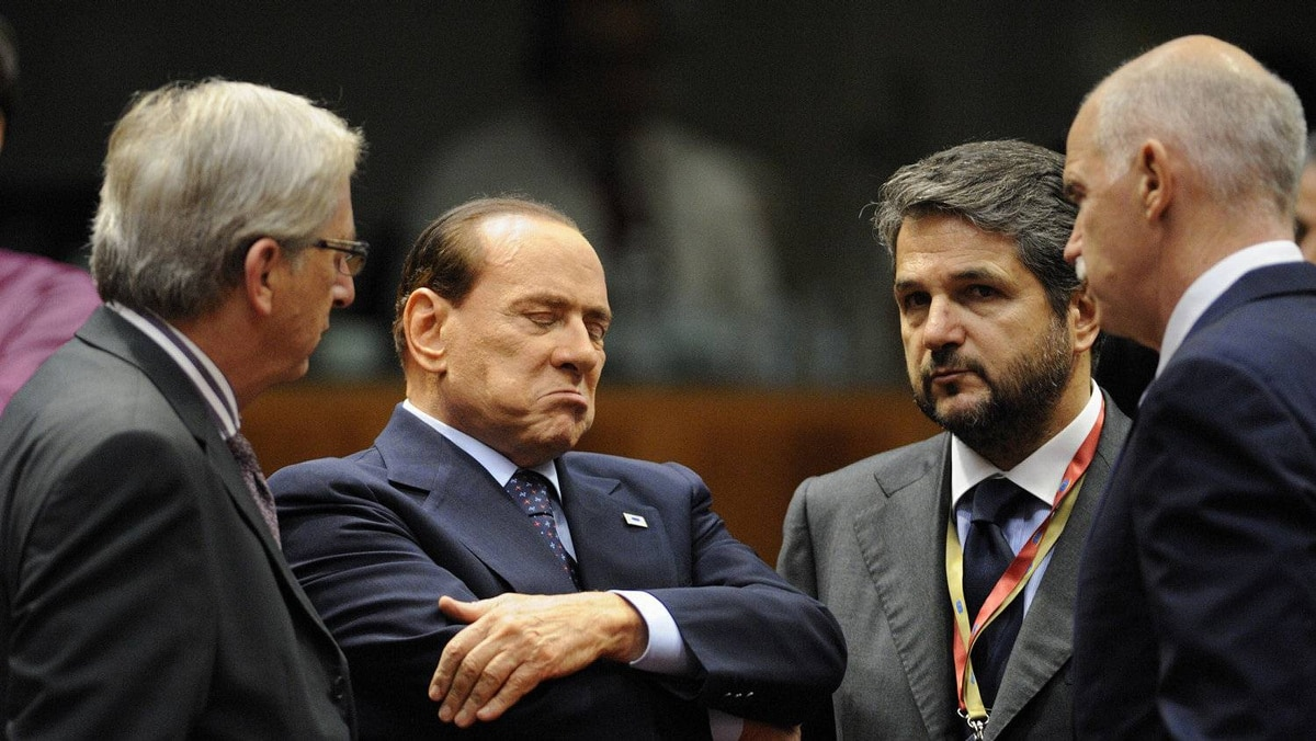 Italian Prime Minister Silvio Berlusconi (second, left) reacts as he talks with Luxembourger Prime Minister Jean-Claude Juncker (L) and Greek Prime Minister George Papandreou (R) during a working session of the European Council at the Justus Lipsius building, EU headquarters in Brussels, on October 26, 2011.