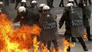 A petrol bomb explodes near riot police during protests against planned reforms by Greece's coalition government in Athens, February 10, 2012.