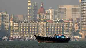 A fishing boat passes the Taj Mahal Hotel in Mumbai.