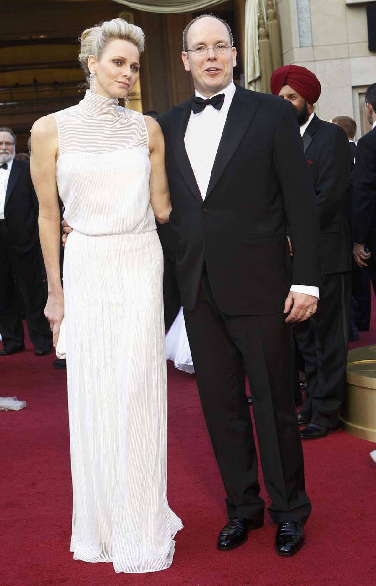 Prince Albert of Monaco keeps a tight grip on his dashing wife Princess Charlene at the Oscars on Sunday.