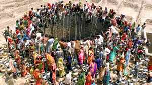 People gather to get water from a huge well in the village of Natwarghad in the western Indian state of Gujarat, in this file picture taken June 1, 2003.