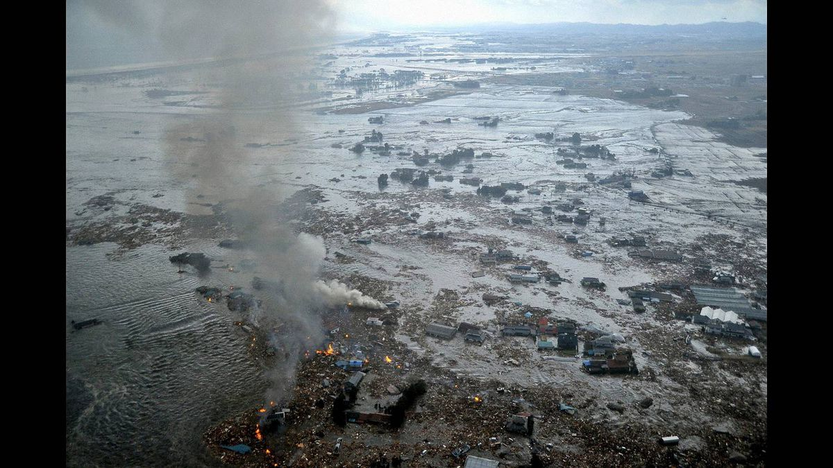 Fires burn in a harbour following an earthquake and tsunami in Natori City, Miyagi Prefecture