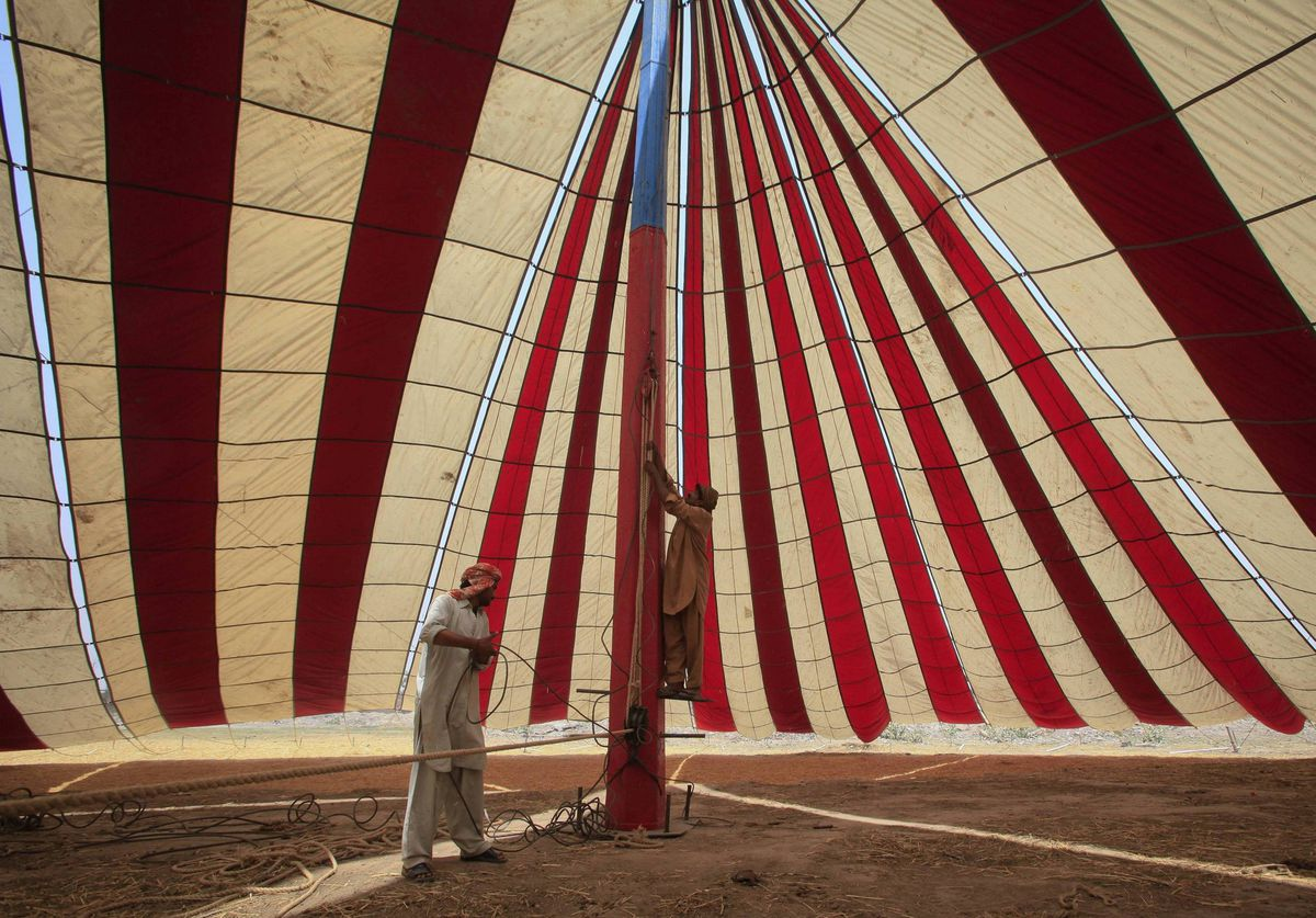 Men prepare a tent for a performance at a circus in Lahore, Pakistan.