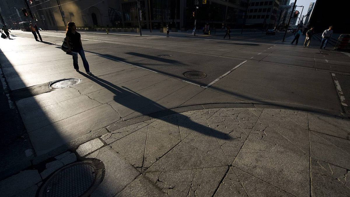 A pedestrian crosses the street at the intersection of King and Bay Streets in the financial district in Toronto on Friday, June 25, 2010. Toronto will host the G20 summit on the weekend.