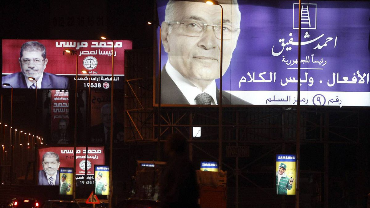 People walk under giant campaign election billboards of presidential candidates former prime minister Ahmed Shafiq (R), and Mohamed Mursi, the head of the Muslim Brotherhood's political party in Cairo May 25, 2012. Egyptians must choose between a Muslim Brother or an ex-military man in a presidential run-off that highlights the stark rifts in a nation united in euphoria when Hosni Mubarak fell 15 months ago, first-round results indicated on Friday. With most votes counted, the Muslim Brotherhood said its candidate Mohamed Mursi had topped this week's polls and would compete in next month's second round with former air force chief Ahmed Shafiq, who served as Mubarak's last prime minister.