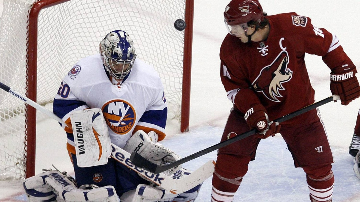 New York Islanders goalie Evgeni Nabokov, left, blocks the puck as Phoenix Coyotes' Shane Doan looks on during the second period of an NHL hockey game on Saturday, Jan. 7, 2012, in Glendale, Ariz. The Coyotes won 5-1. (AP Photo/The Arizona Republic, Emmanuel Lozano )