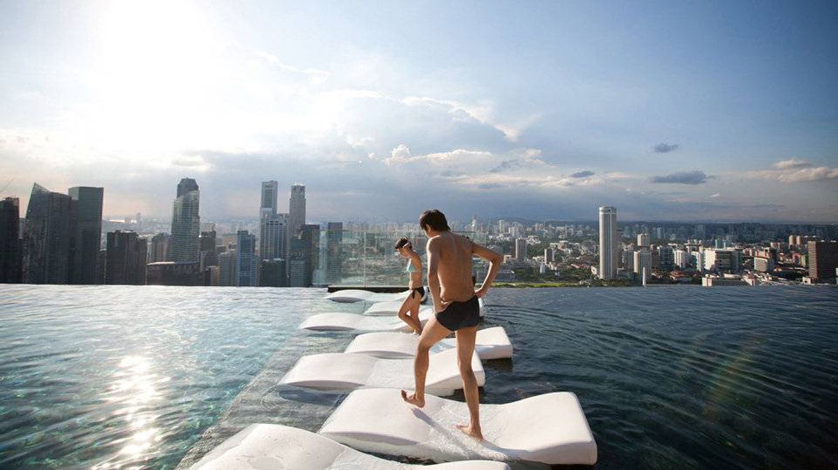 Hotel guests are seen at the infinity pool at the SkyPark atop Marina Bay Sands in Singapore, on Tuesday, Feb. 28, 2012.
