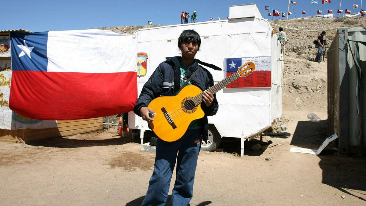 A young man plays guitar at the encampment beside the San Jose mine, near the city of Copiapo, 800 km north of Santiago on October 12, 2010.