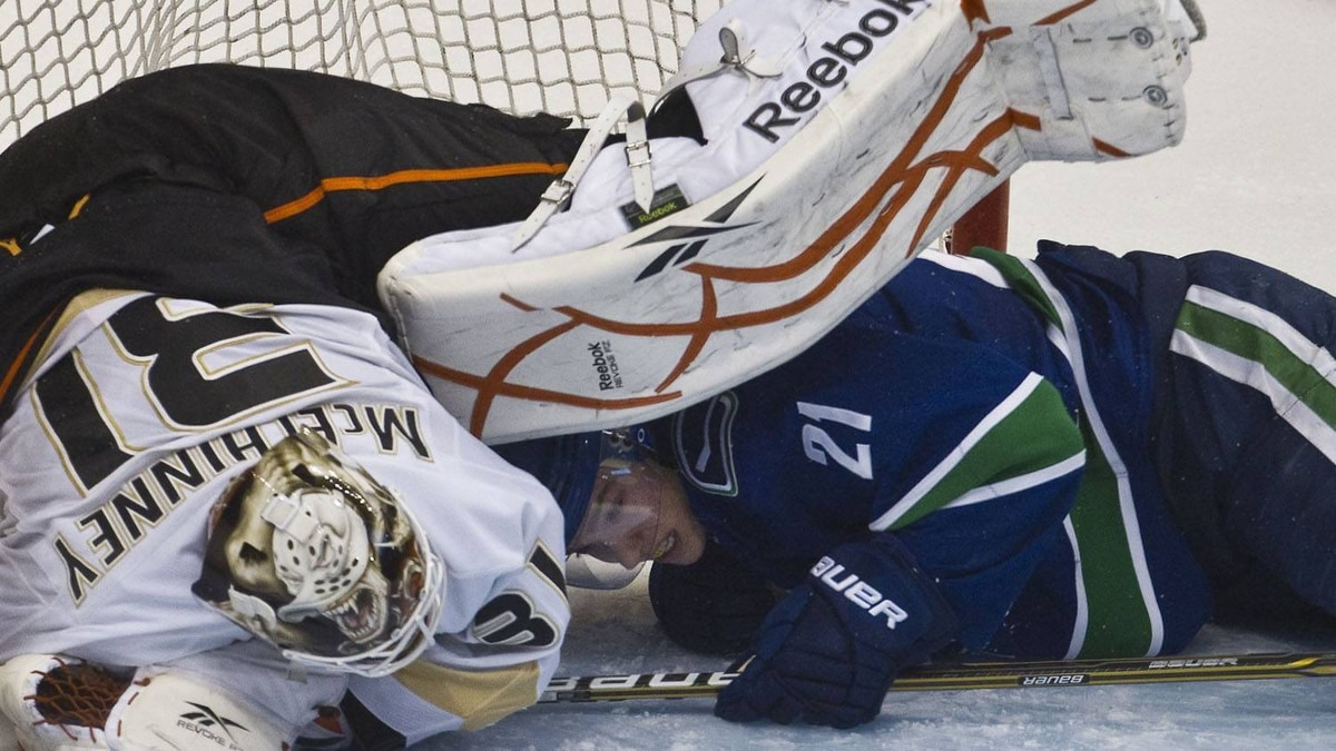 Anaheim Ducks goaltender Curtis McElhinney (L) falls over Vancouver Canucks Mason Raymond during the third period of their NHL hockey game in Vancouver, British Columbia December 8, 2010. REUTERS/Andy Clark