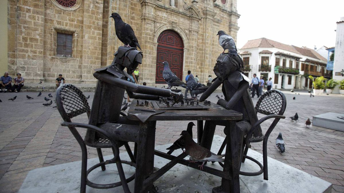 Pigeons stand on a sculpture of chess players on April 11, 2012, inside Cartagena's old city. Colombia plays host to the Summit of the Americas from April 14 to 15.