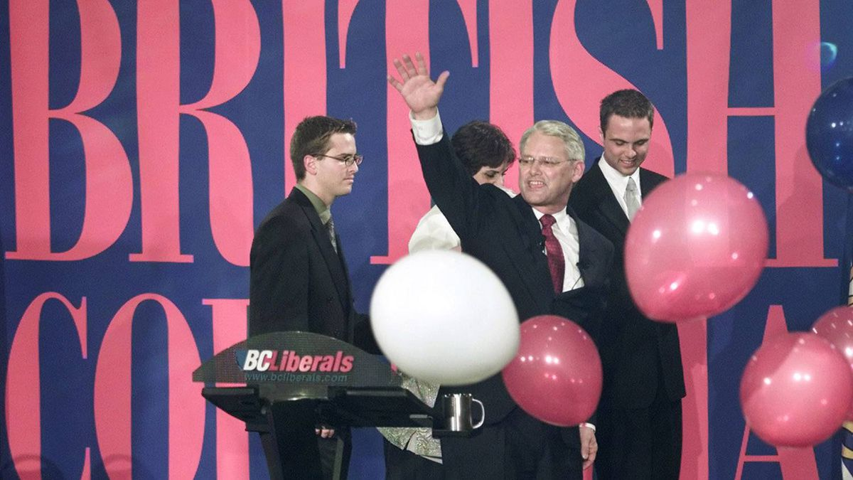 British Columbia Liberal leader Gordon Campbell waves to a cheering crowd as he makes way off the stage followed by his son Nick, left, wife Nancy, and eldest son Geoff after making his victory speech in Vancouver May 16, 2001. Mr. Campbell's Liberals defeated the ruling New Democrat Party in a landslide.