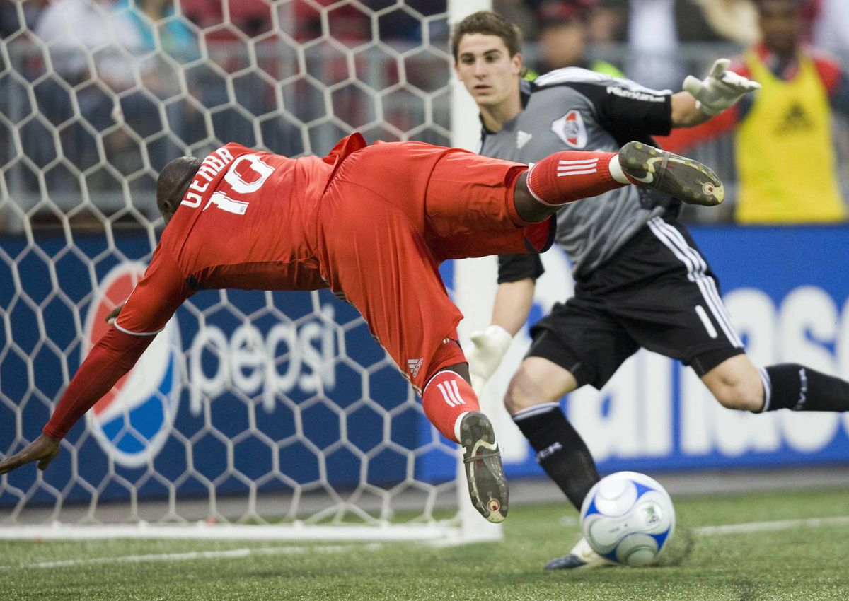 Toronto FC forward Ali Gerba falls as he attempts to shoot against River Plate goalkeeper Daniel Vega during a friendly match in Toronto on Wednesday July 22, 2009.
