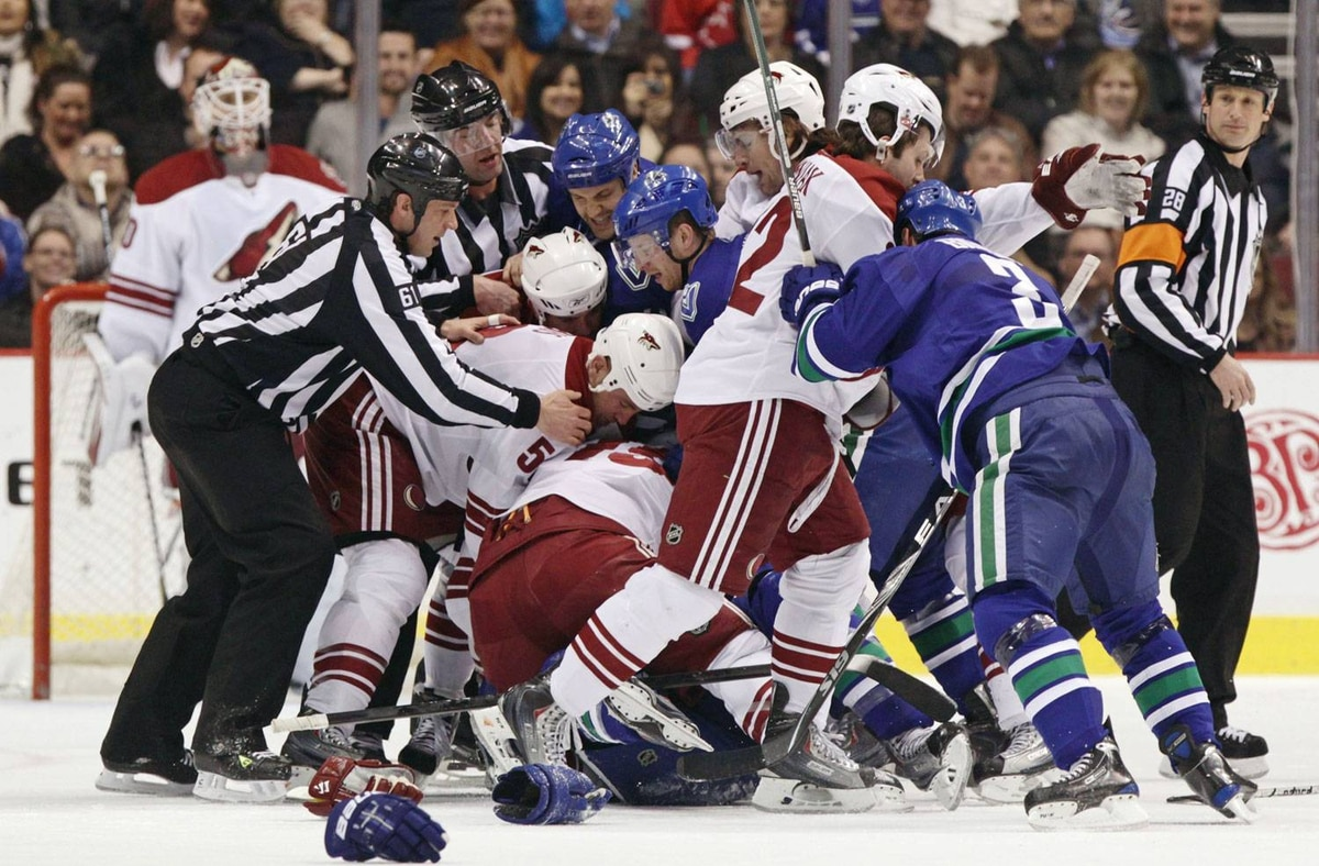 Officials try to restore order as members of the Vancouver Canucks and Phoenix Coyotes fight during first period NHL action in Vancouver. Darryl Dyck/The Canadian Press