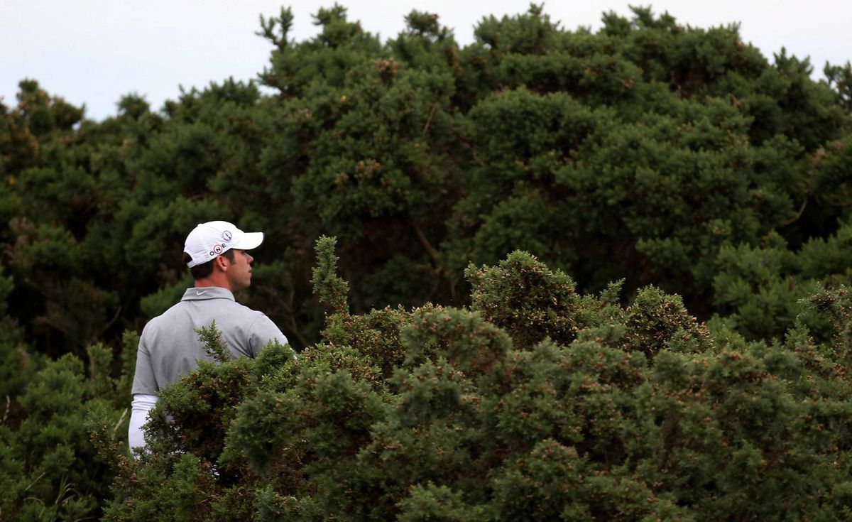Paul Casey of England looks for his drive in the gorse bush on the 12th hole