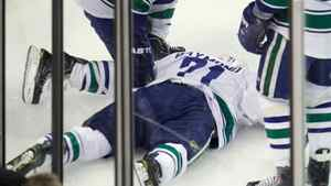 Vancouver Canucks' Sami Salo (6) and Chris Higgins, right, check on Mason Raymond (21), who was hit hard into the boards by Boston Bruins defenseman Johnny Boychuk during the first period in Game 6 of the NHL hockey Stanley Cup Finals in Boston, Monday, June 13, 2011.