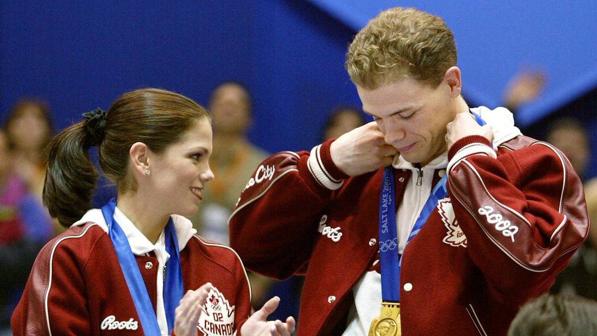 Canada's Jamie Salé applauds as her partner David Pelletier adjusts his gold medal during medals ceremonies at the Olympic Winter Games in Salt Lake City, Utah, Sunday, Feb. 17, 2002. The Canadian pair shares the gold medal with Russia's Elena Berezhnaya and Anton Sikharulidze following a controversy in the judging of the competition.