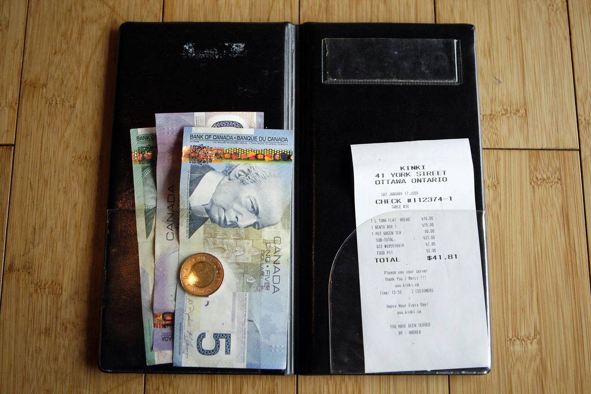 A bill is paid in cash at an Ottawa restaurant.