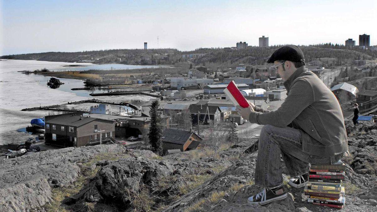 John Mutford reads a book overlooking Yellowknife Bay in Yellowknife, N.W.T.