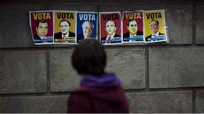 Fake electoral posters showing the faces of the Spanish bank presidents Angel Ron, Pedro Guerrero, Francisco Gonzalez, Emilio Botin, Jose Maria Arias y Antonio Basagoiti, from left to the right, are seen on a wall near Catalunya square in Barcelona city, Spain, Saturday Nov. 12, 2011.