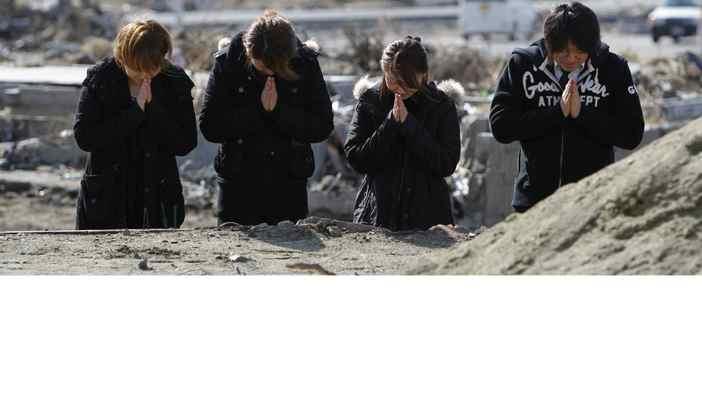 Madoka Sato, Hiroko Sato, Haruka Tsubonuki and her husband, Kazuhiro, pray early Sunday for their grandmother Fumiko Mori, who was killed in the March 11 earthquake and tsunami.