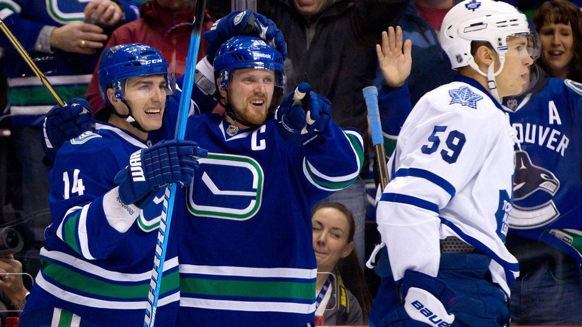Vancouver Canucks' Alex Burrows, from left, and Henrik Sedin, of Sweden, celebrate Burrows' goal as Toronto Maple Leafs' Keith Aulie skates to the bench during the first period of an NHL hockey game in Vancouver, B.C., on Saturday February 18, 2012. The Canucks won 6-2. THE CANADIAN PRESS/Darryl Dyck