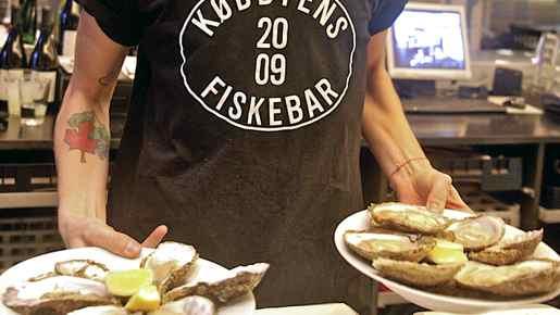 A waiter serves oysters at Kodbyens Fiskebar in Copenhagen.
