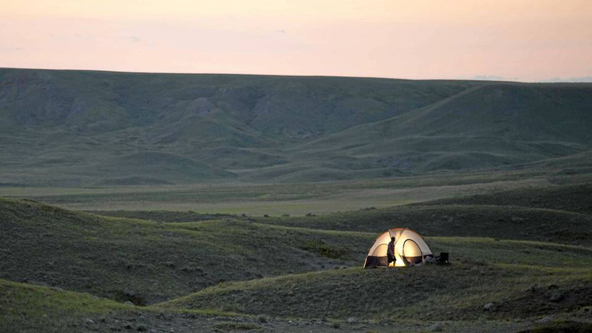 A lone tent casts a glow in Grasslands National Park.