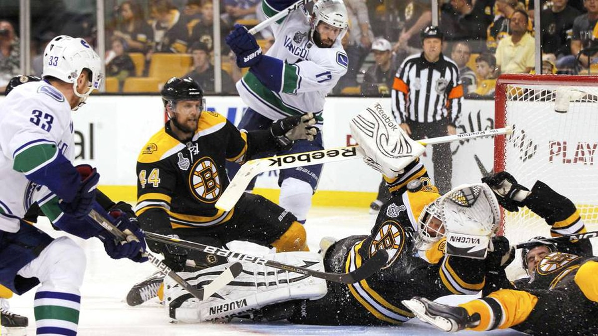 Vancouver Canucks centre Henrik Sedin shoots the puck over Boston Bruins goalie Tim Thomas and Daniel Paille to score during the third period in Game 6 of the NHL Stanley Cup hockey playoff in Boston.