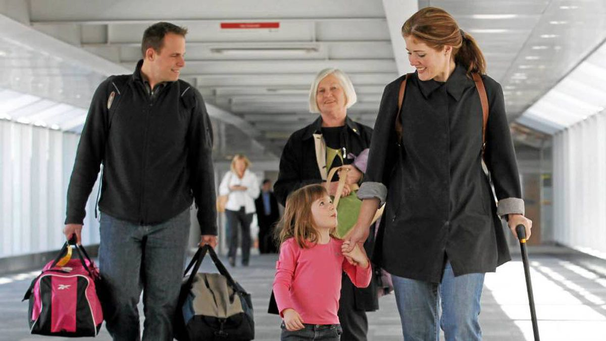 Paulette O'Leary, right, holds her daughter Payton's hand as they and her husband, Jason Schuy, and mother Ruth O'Leary walk at Toronto's Pearson International Airport on Wednesday.