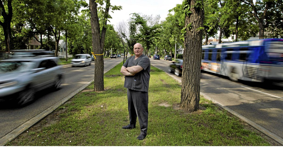 """Randy Crowell stands on a meridan near a tree with a yellow ribbion, tied in support of Canadian soldiers on 97 St. in Edmonton, on June 27, 2011. Mr. Crowell wants to rename the street """"Heroes Blvd."""""""