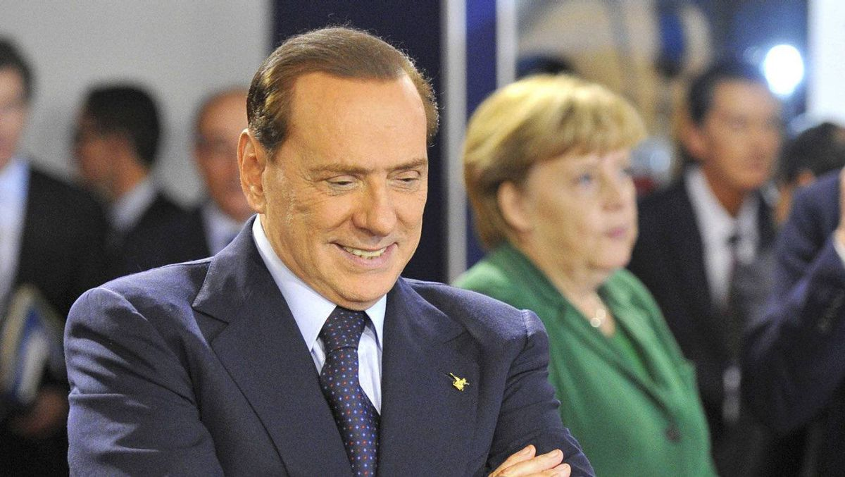 Italy's Prime Minister Silvio Berlusconi walks past Germany's Chancellor Angela Merkel before a working session at the G20 Summit of major world economies in Cannes November 3, 2011.