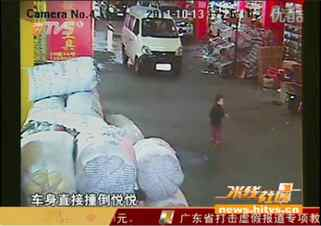 A screen shot from Chinese television shows a toddler just before he is struck by a van. 18 people ignored the badly injured child after the accident.