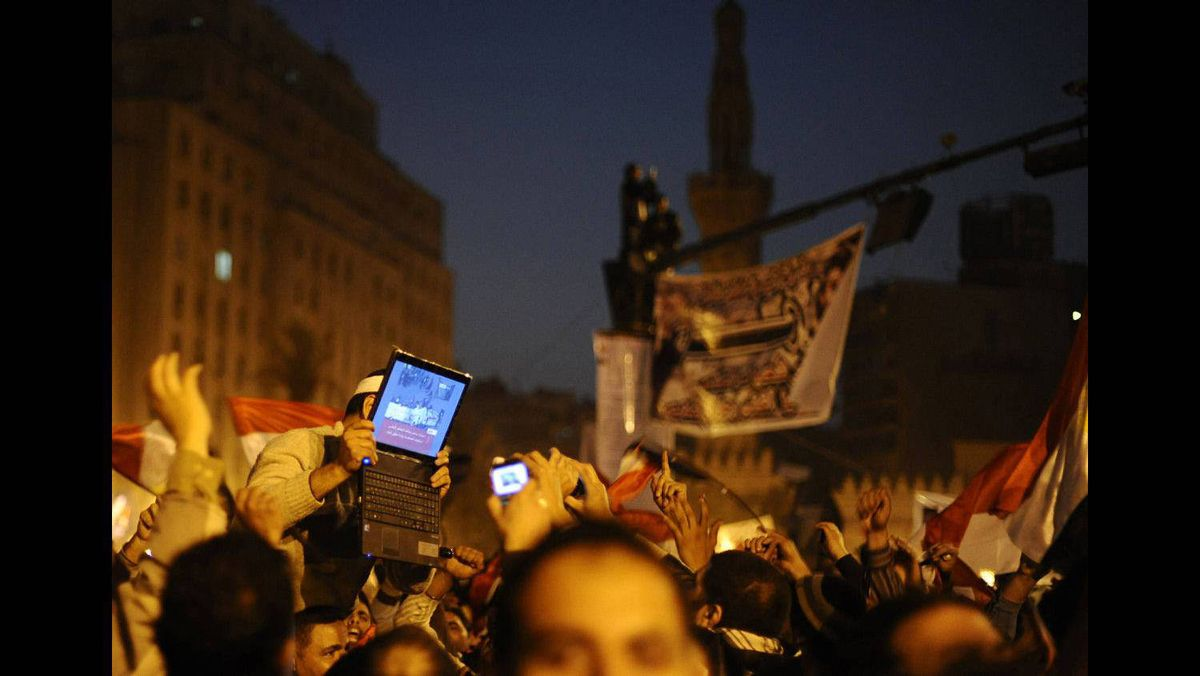 An opposition supporter holds up a laptop showing images of celebrations in Cairo's Tahrir Square, after Egypt's President Hosni Mubarak resigned February 11, 2011.