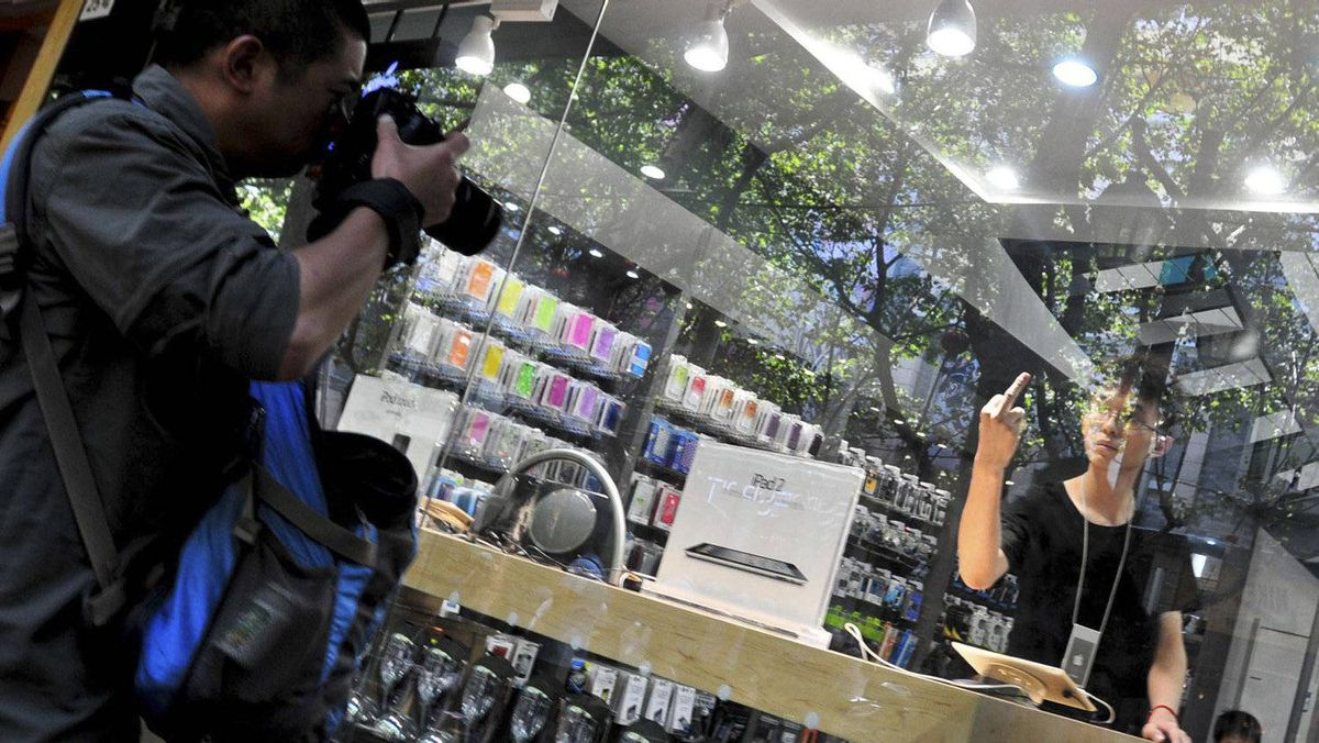 An employee in a fake Apple Store gestures with his middle finger to a photographer trying to take pictures of the store in Kunming, Yunnan province July 21, 2011.
