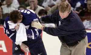 Toronto Maple Leafs Bryan Berard is assisted off the ice by a team trainer following a blow to the face in second period NHL action against the Ottawa Senators at the Corel Centre in Kanata, Ont. Saturday, March 11, 2000.