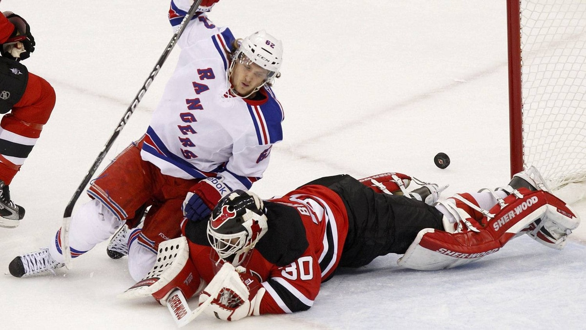 New York Rangers' Carl Hagelin (L) falls on New Jersey Devils goalie Martin Brodeur as he makes a save during the first period in Game 6 of their NHL Eastern Conference Final game in Newark, New Jersey, May 25, 2012.