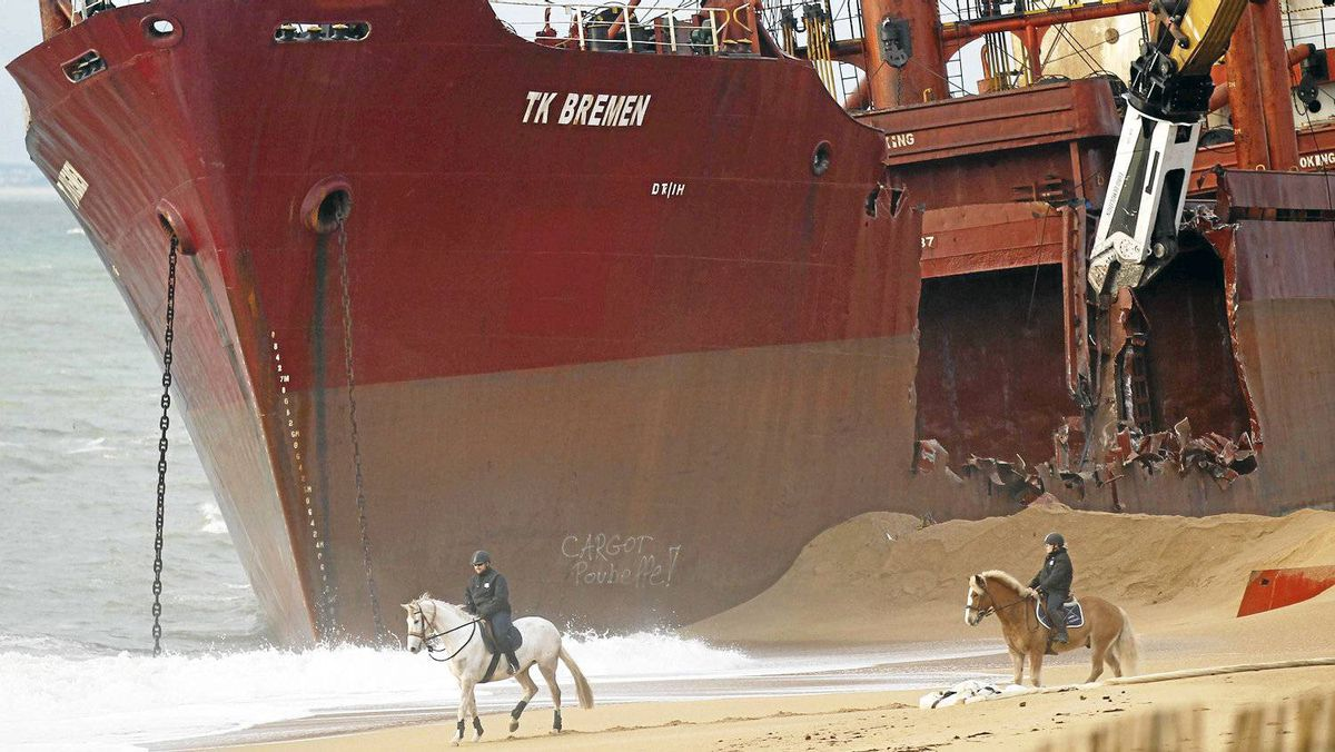 """Security officers look on from their horses as a crane dismantles the Maltese-registered cargo ship the TK Bremen. A spokesman for the maritime prefecture said:""""We can't take the risk of towing it, as there is a danger of it breaking up and becoming more difficult to remove. Strictly-speaking, the shipowner has the right to repair the vessel where it lies,"""" he added, """"but it appears it struck several rocks and its hull has been perforated in several places. The most probable outcome is that the ship will be dismantled."""""""